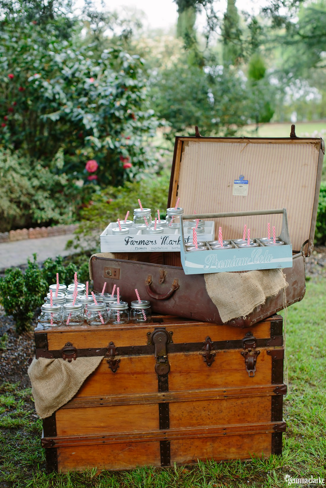 Glass jars with straws through the lid, some in wooden boxes and on a suitcase and a wooden chest
