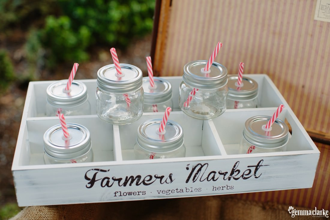 Glass jars with straws through the lids in a small wooden crate