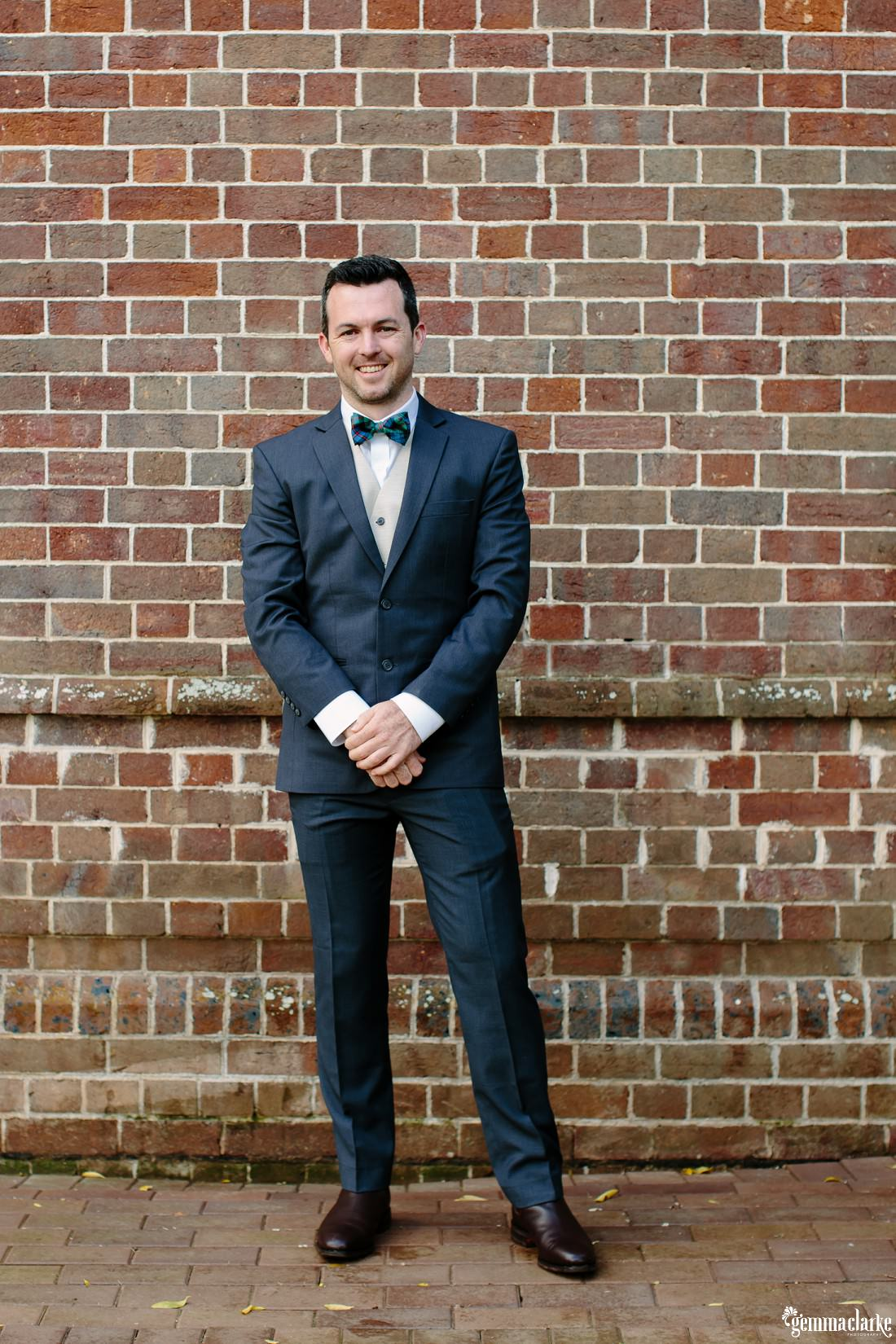 A groom in a navy suit with a white shirt, beige vest and tartan bowtie standing in front of a brick wall