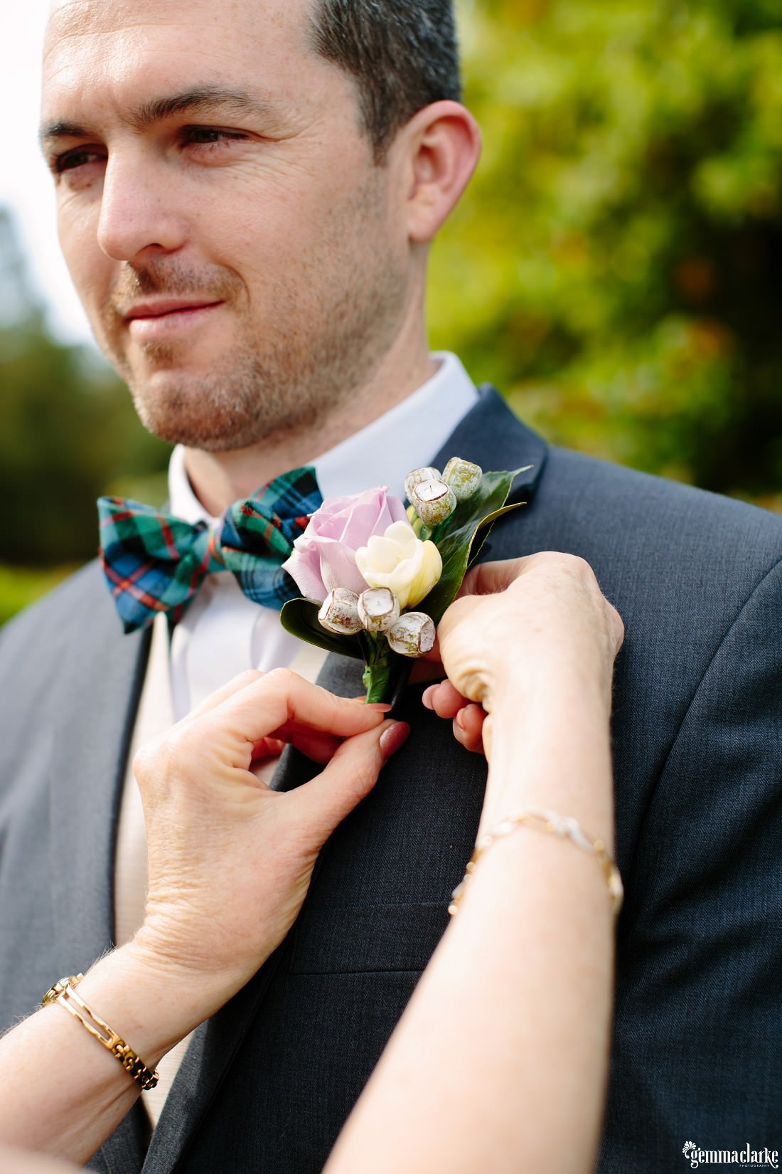 A closeup of a groom having his floral buttonhole adjusted