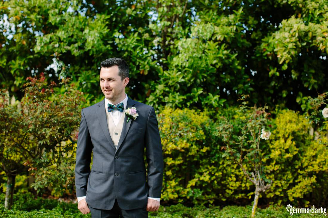 A groom standing in front of a hedge and some trees