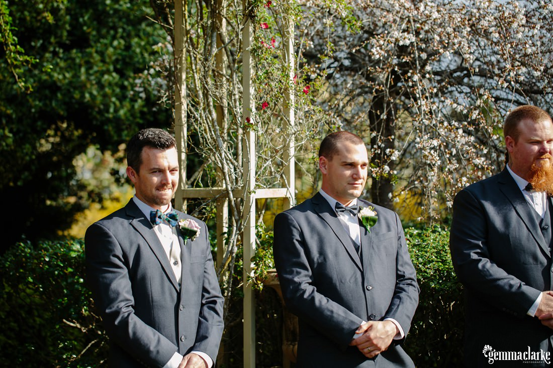 A groom and his groomsmen waiting as the bride comes down the aisle