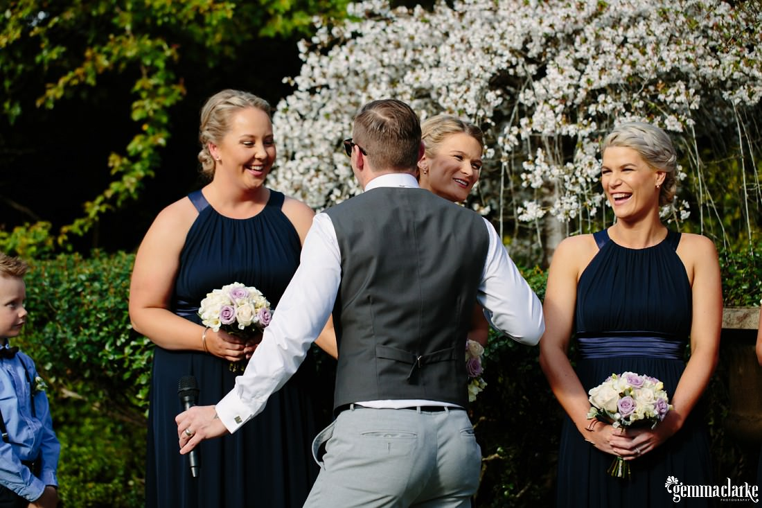 A speaker at a wedding gives a kiss to each bridesmaid as he makes his entrance