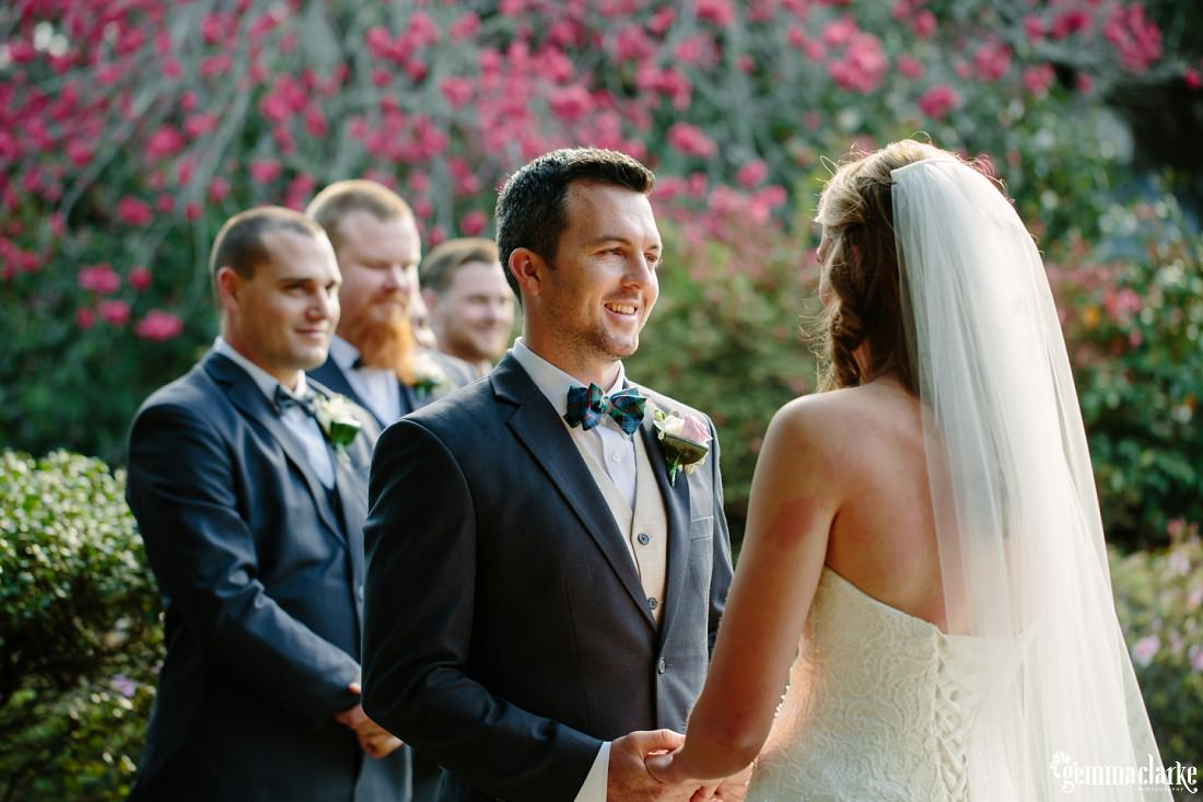 A groom smiles and looks lovingly into his brides eyes