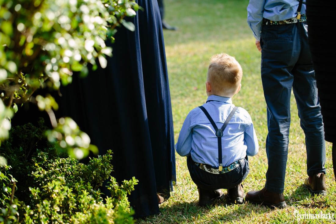 A young boy crouching at a wedding ceremony