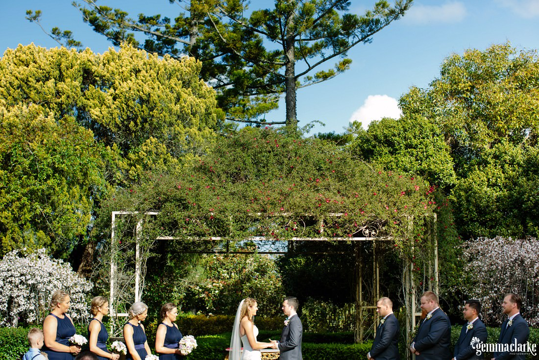 A bride and groom holding hands at their ceremony with their bridal party either side with greenery and trees in the background