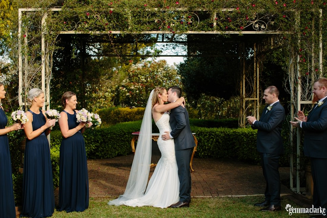 Bridesmaids and groomsmen clap as the bride and groom kiss at their ceremony