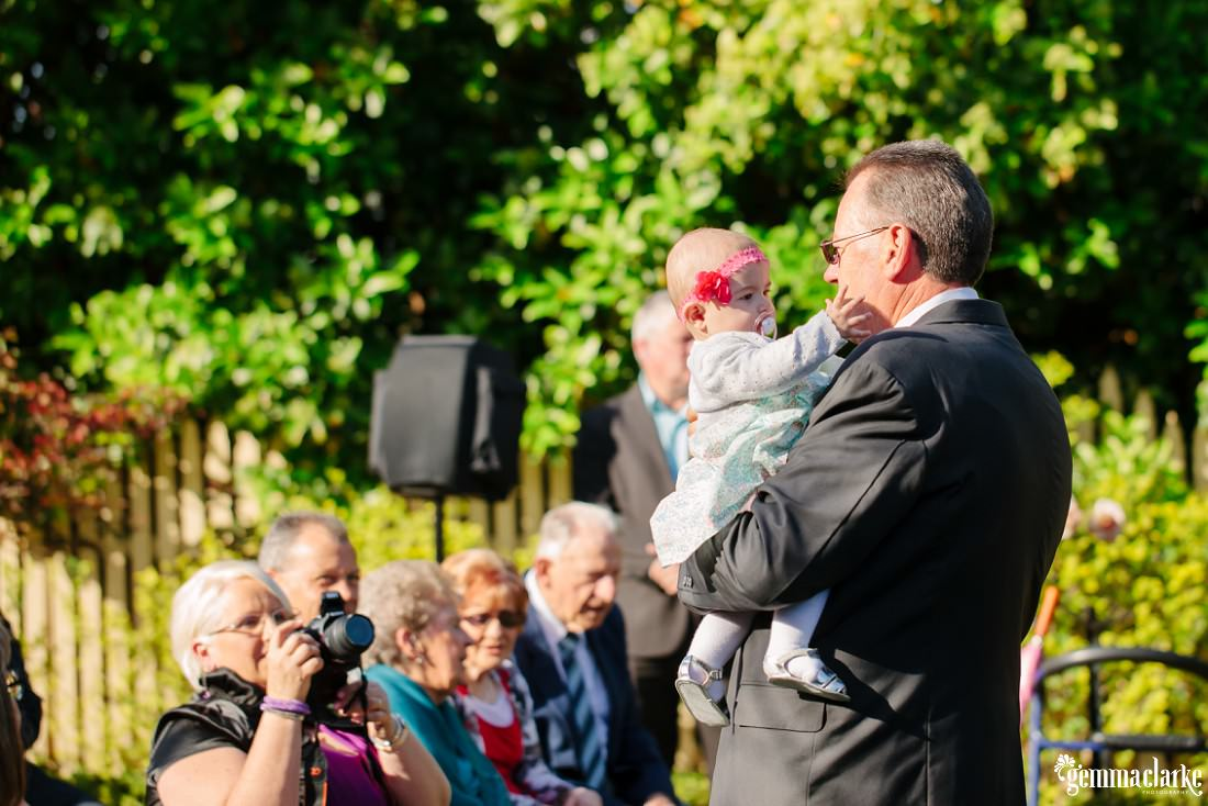 The bride's father holding a baby