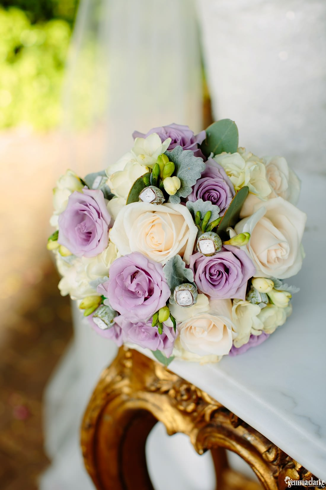 A close up of a bridal bouquet on a marble table