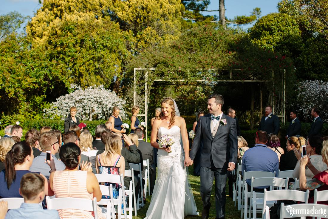 Wedding guests taking photos on their phones as the bride and groom walk back down the aisle