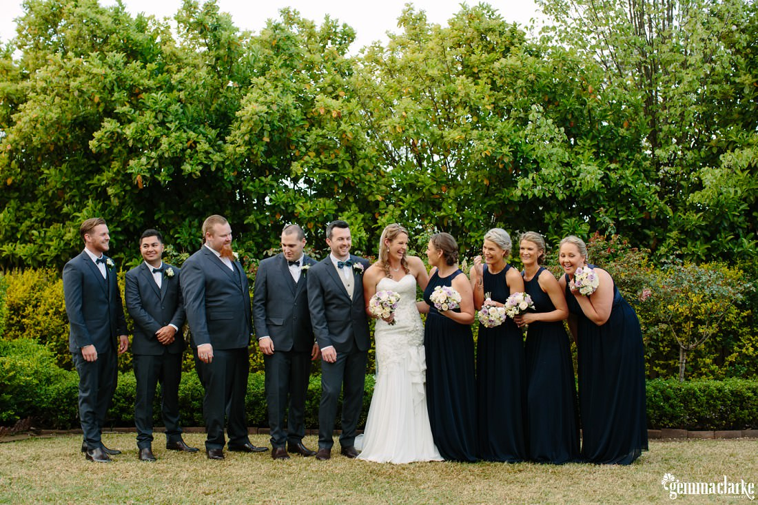 A bide and groom and their wedding party standing in a row and smiling