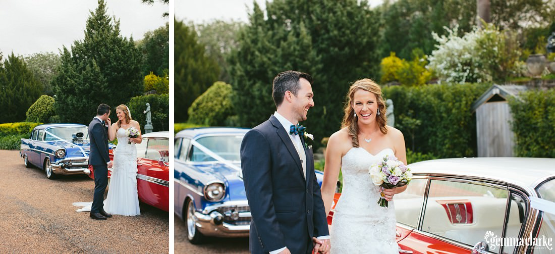 A bride and groom smiling and standing together next to two vintage American cars