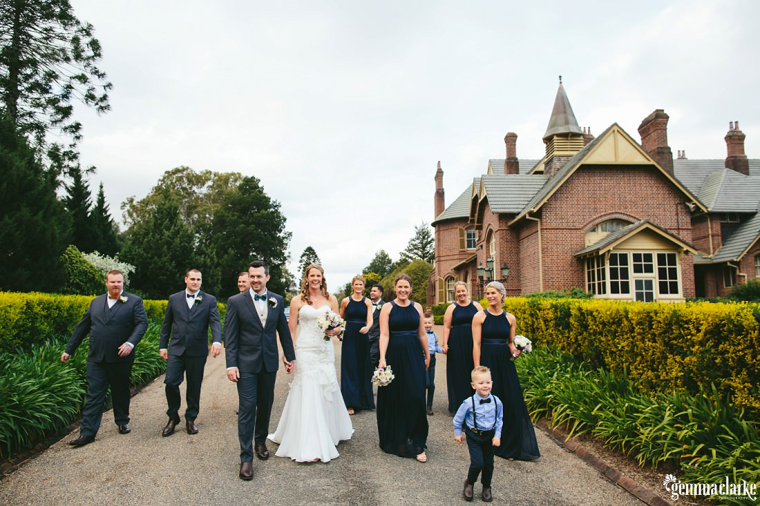 A bride and groom and their wedding party walking down a driveway between hedges