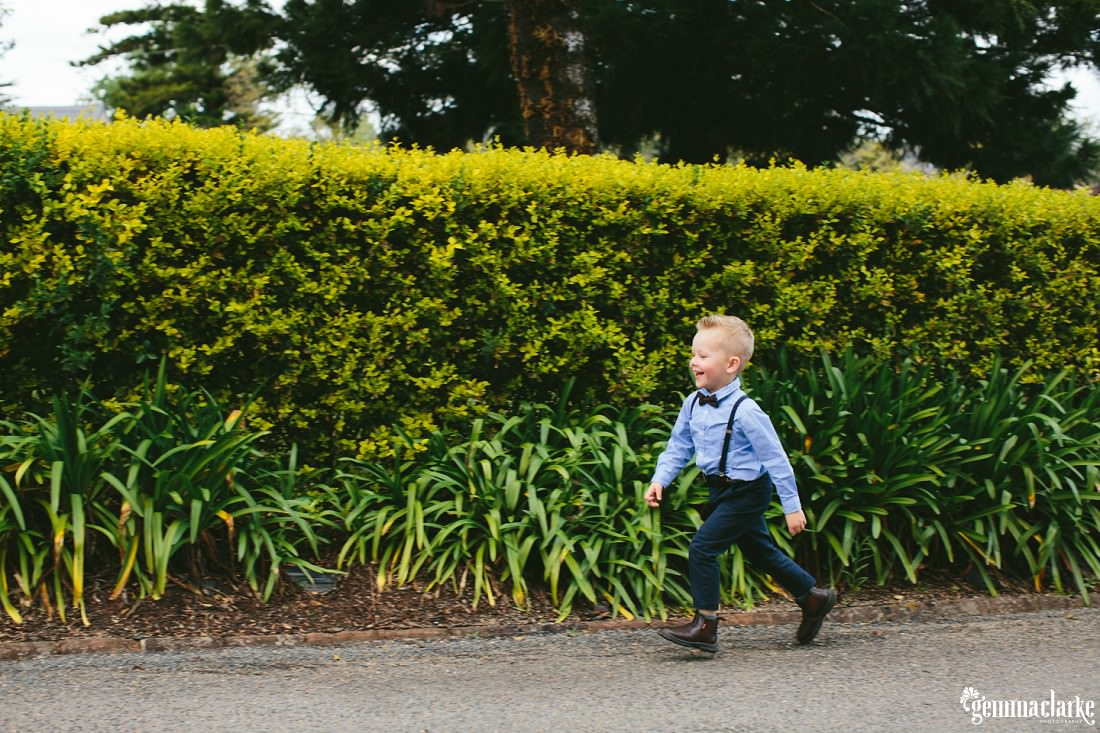 A smiling young boy runs along a path in front of a hedge