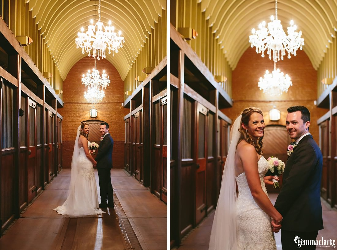 A bride and groom holding hands and looking back over their shoulders in a corridor with chandeliers above