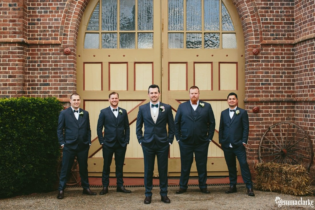 A groom and his groomsmen stand with hands in pockets in front of a double wide arched door