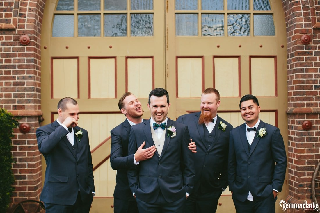 A groom and his groomsmen horsing around in front of a double wide arched door