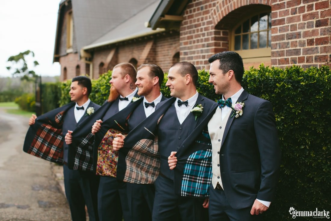 A groom and his groomsmen showing off the individual patterns in the lining of their coats