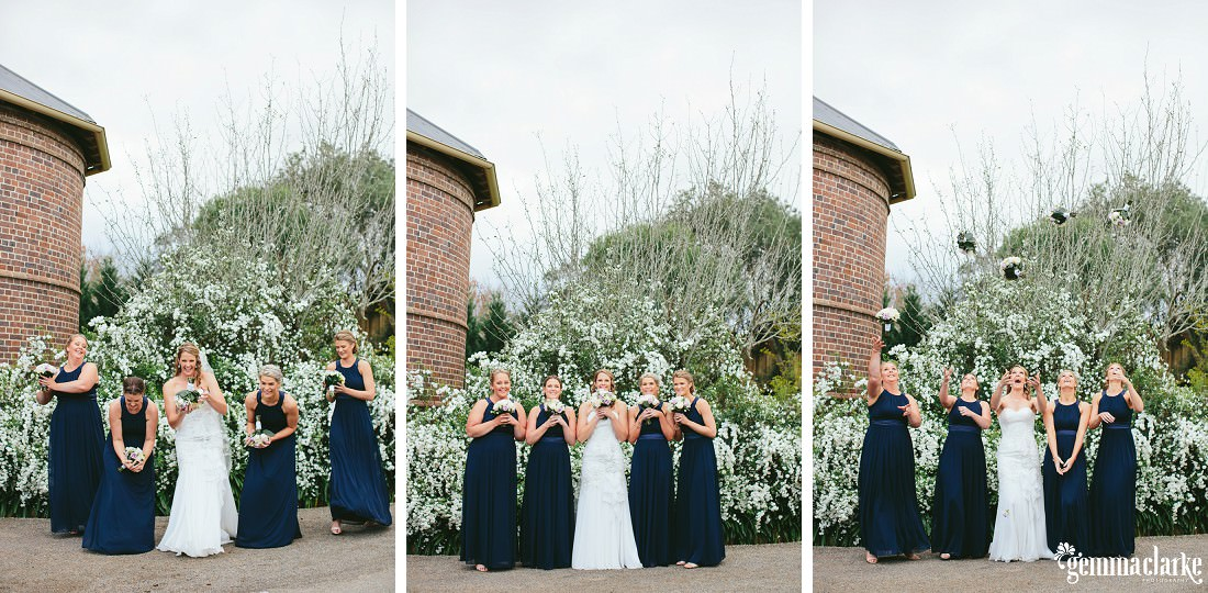 A bride and her bridesmaids posing and throwing their bouquets in the air