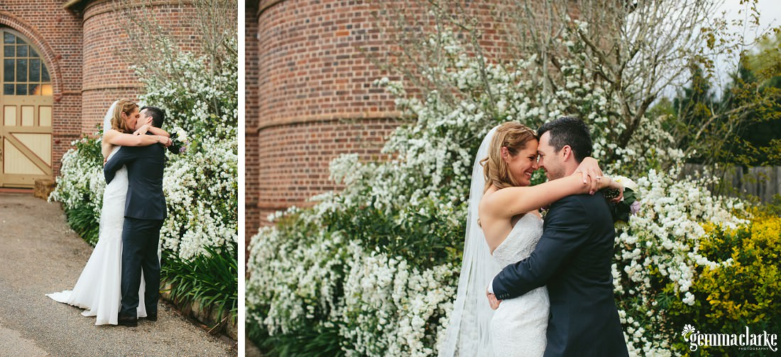 A bride and groom embrace and share a kiss in front of some white flowers