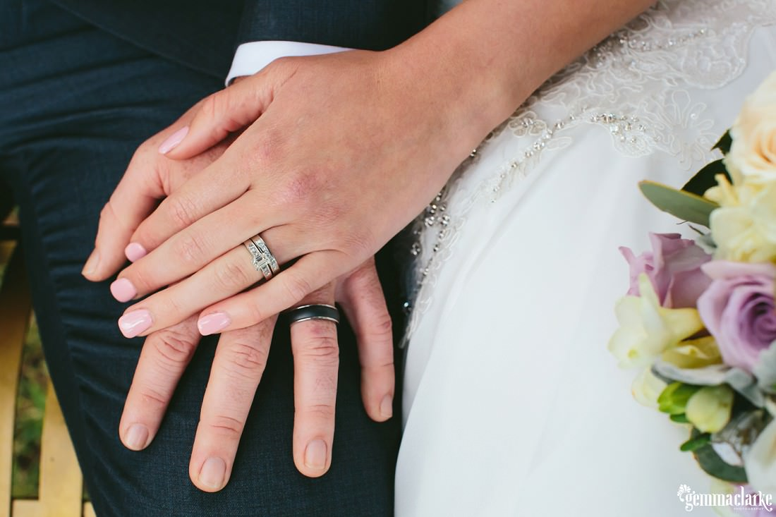 A close up of a bride and groom's hands showing off their rings