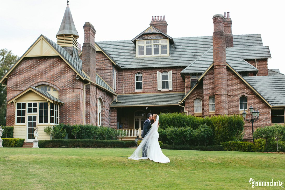 A bride and groom kiss on the lawn in front of Camelot