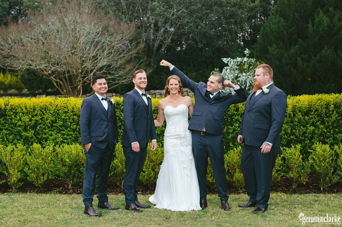 "A bride standing with four groomsmen, one doing a ""bodybuilding"" pose"