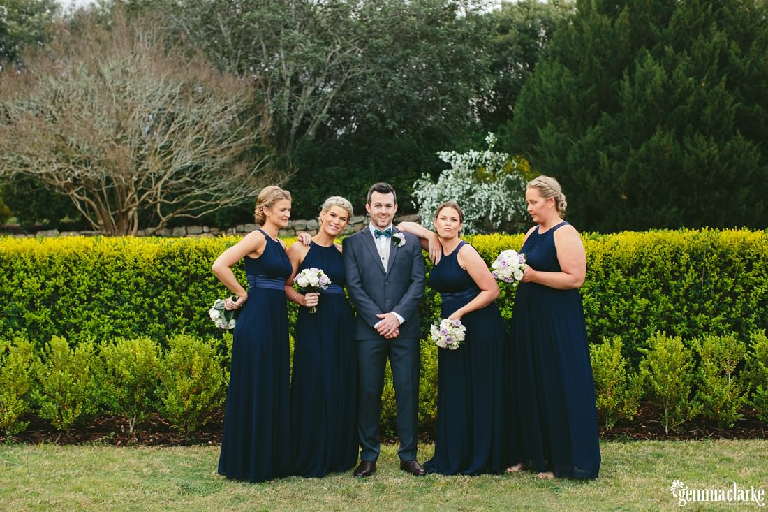 A groom standing with four posing bridesmaids