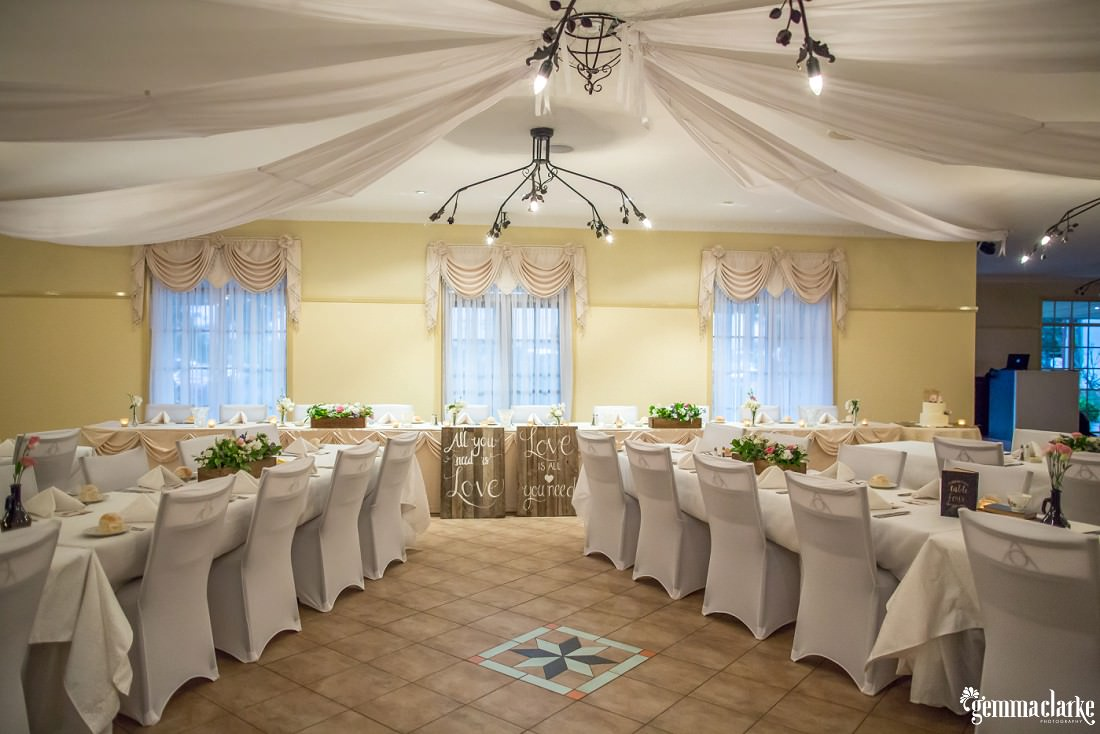 A reception setup with white tables and chairs
