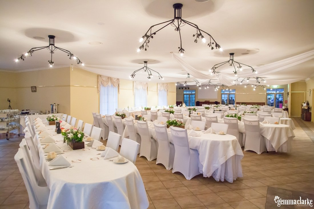 A wedding reception setup with white tables and chairs and floral centrepieces