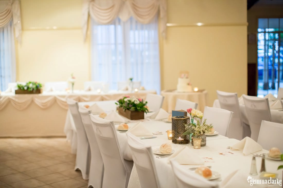 A wedding reception setup with white tables and chairs, soft warm lighting and floral centrepieces