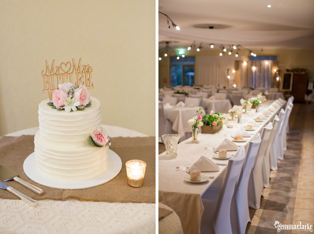 A white two tiered wedding cake with floral decorations and a topper with the bride and groom's names, and the bridal table