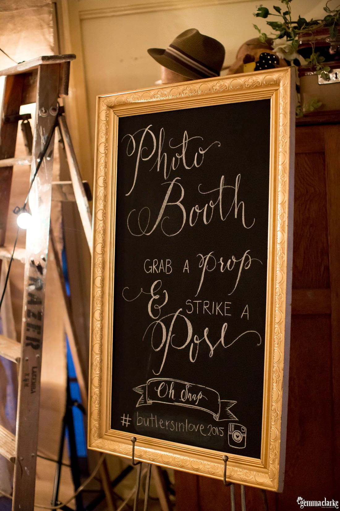 A framed blackboard with chalk writing announcing the photo booth