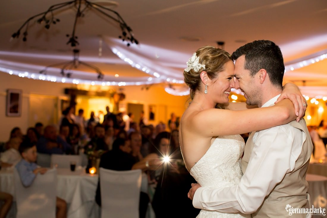 A bride and groom dancing close at their reception