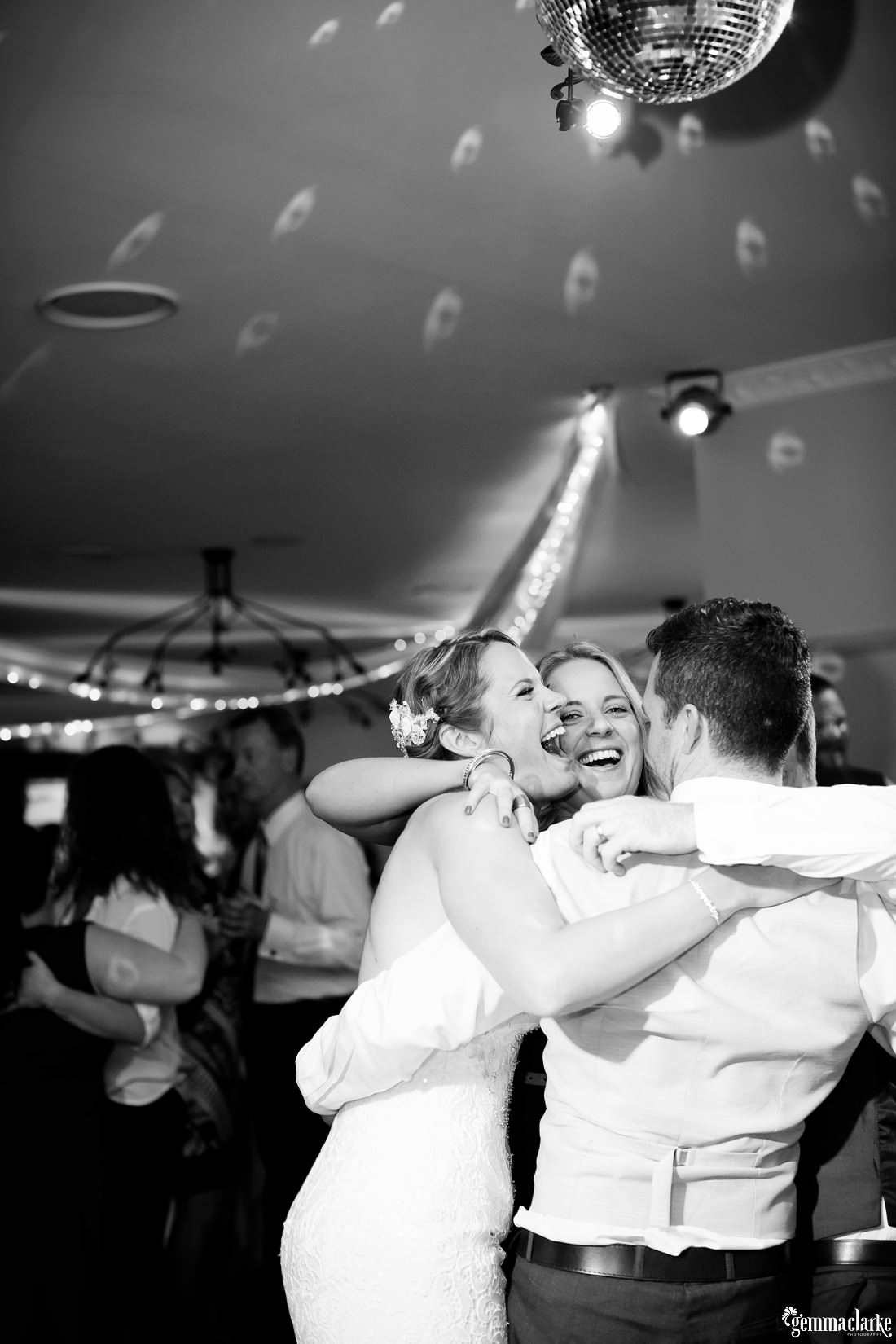 A bride and groom getting a hug from a guest on the dancefloor