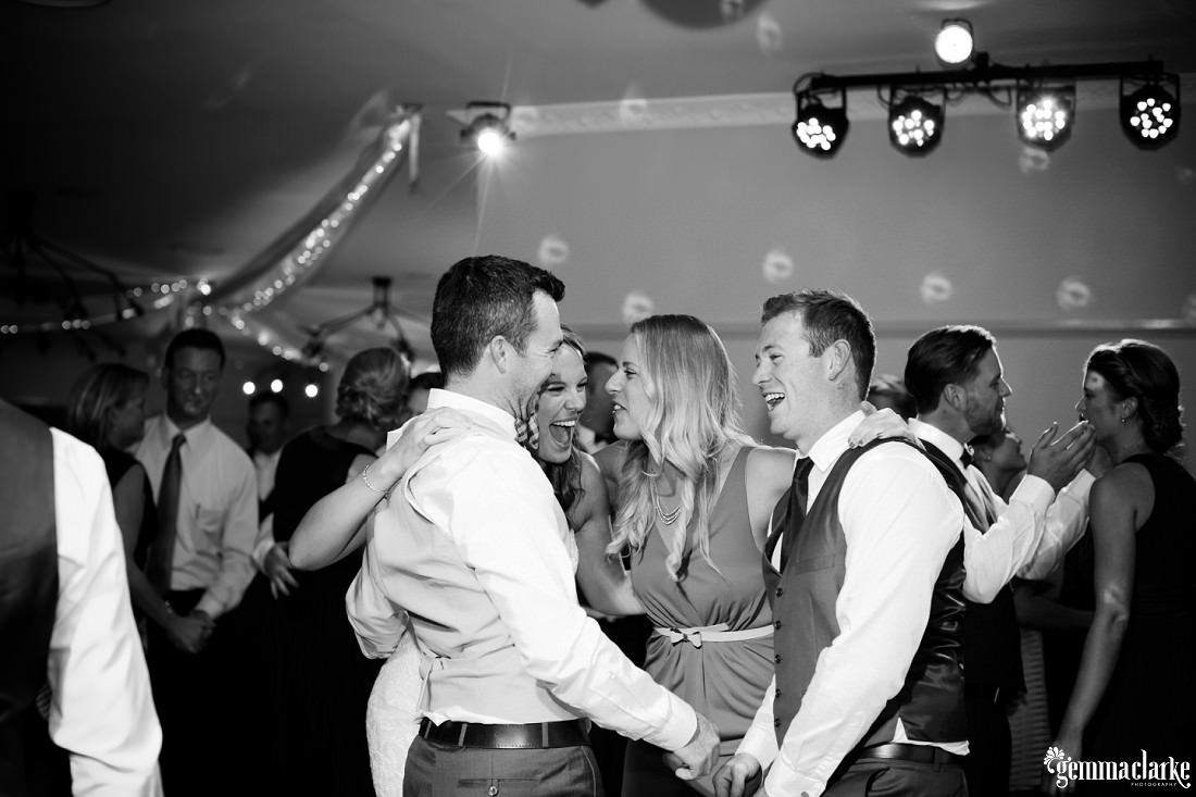 A bride and groom laughing with guests on the dancefloor
