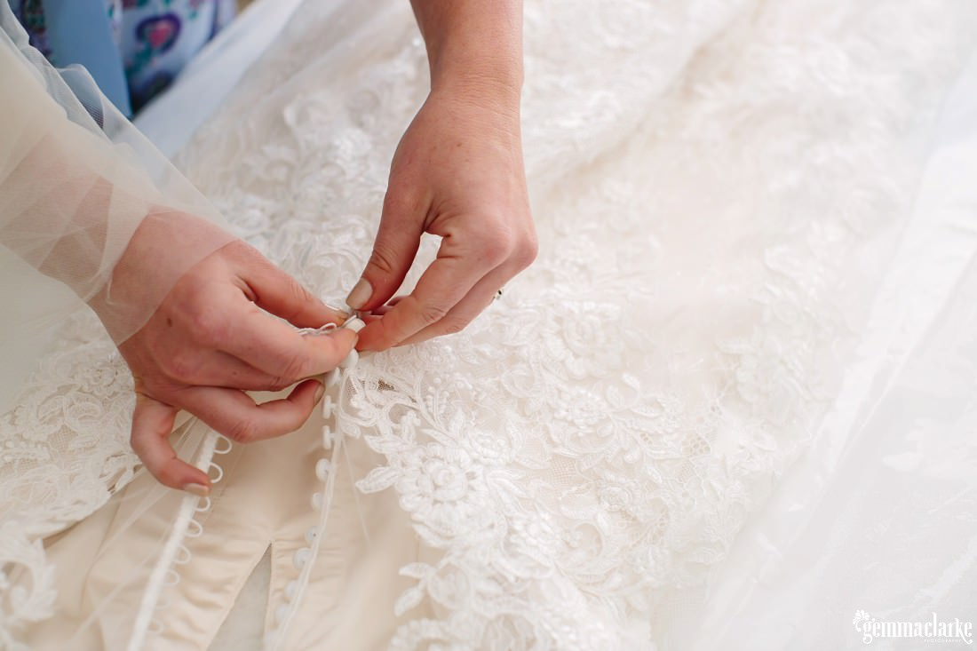 Buttoning up a bridal gown