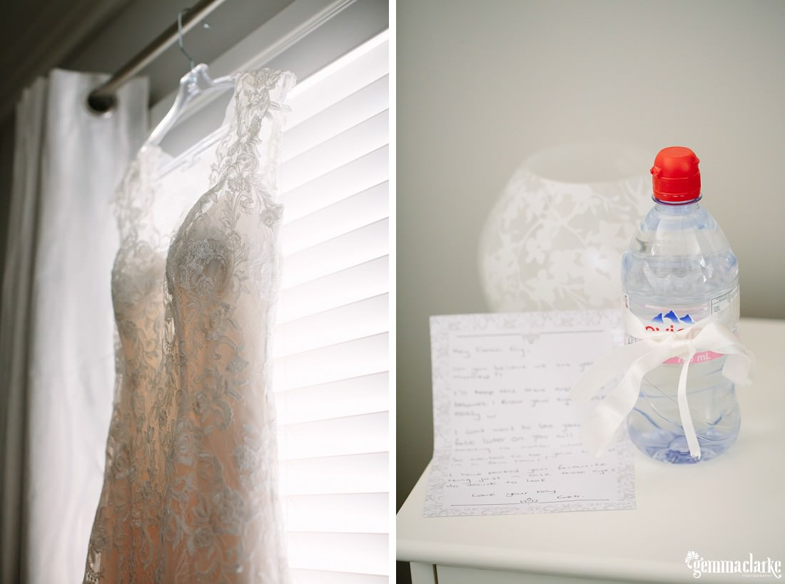 A wedding gown on a hanger in a window, a water wrapped in a white ribbon and some handwritten notes