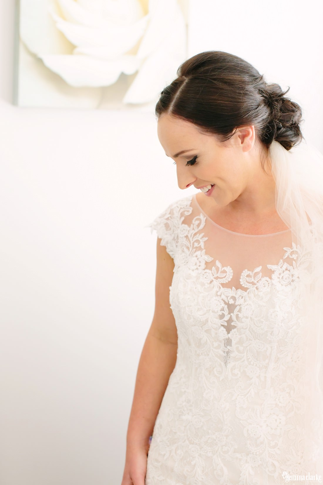 A bride smiling and looking down at her dress