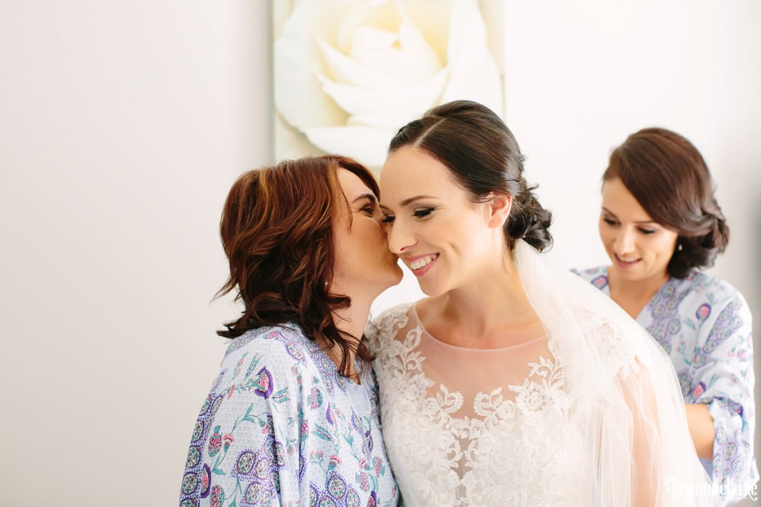 A bride's mother kisses her daughter on the cheek
