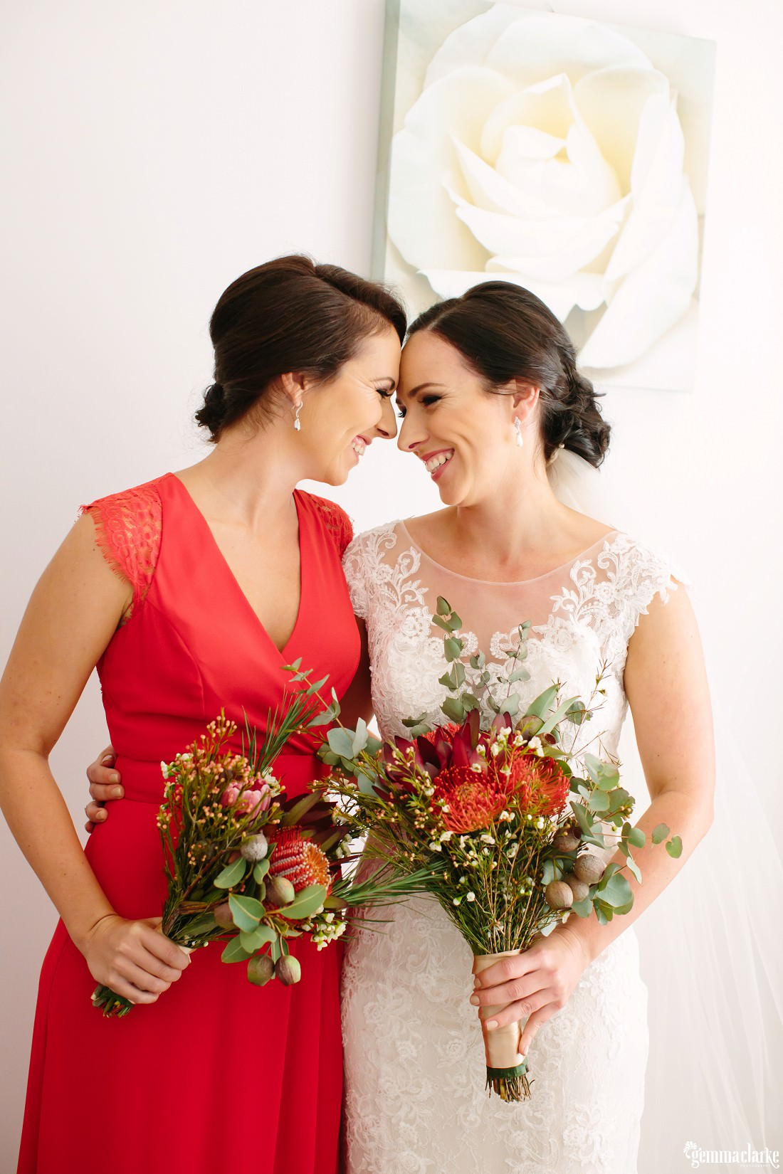 A bride and bridesmaid eskimo kiss while holding bouquets of native Australian flowers