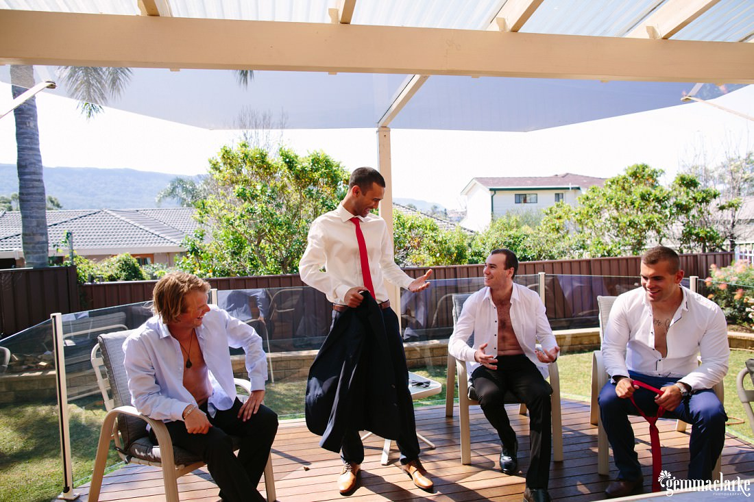 A groom and his groomsmen getting ready for the wedding on a deck