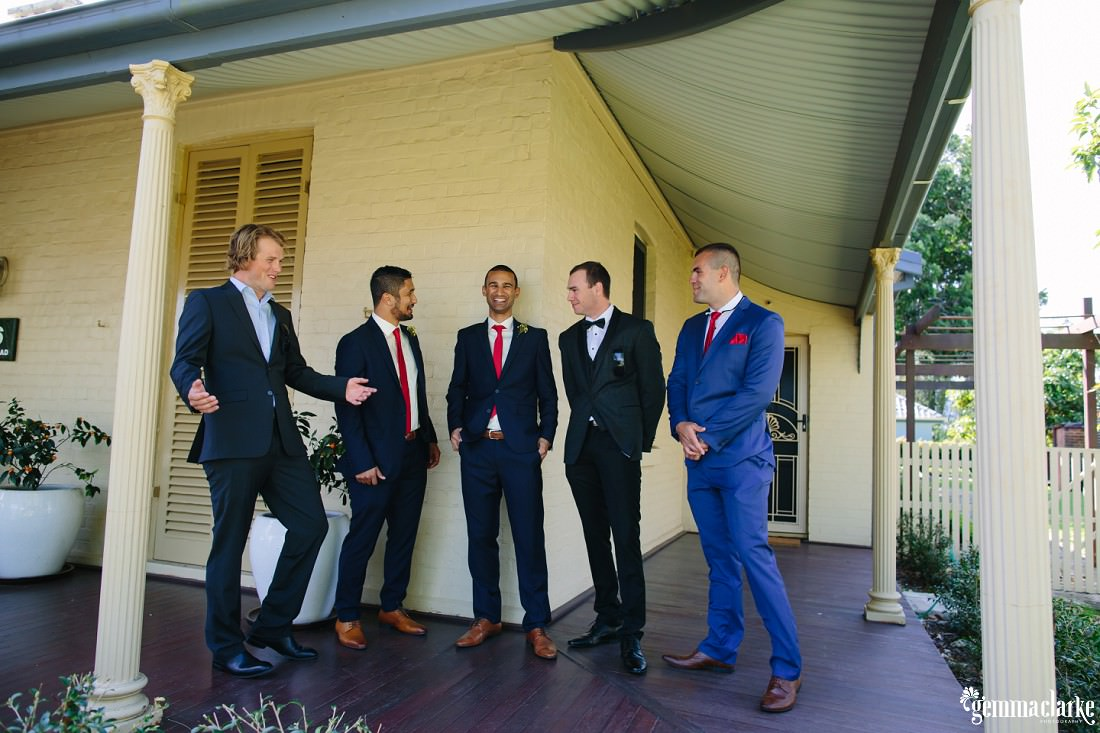 A groom and his groomsmen posing together on a verandah