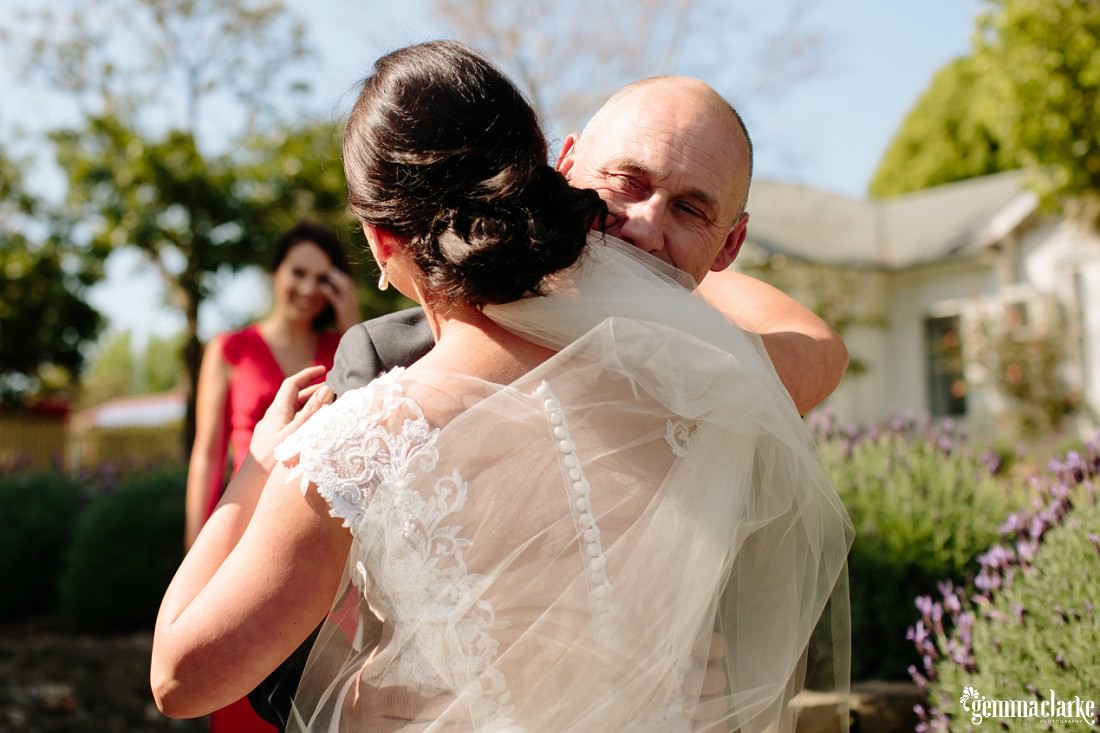 A bride gets a hug from her father