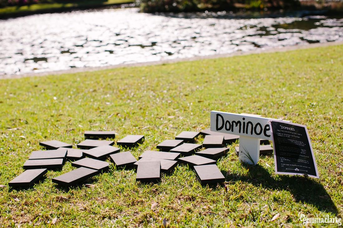 Large dominoes on a lawn in front of a pond