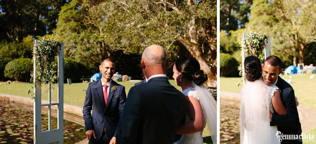 A bride's father hands his daughter over to her smiling groom, and the groom gives her a big hug