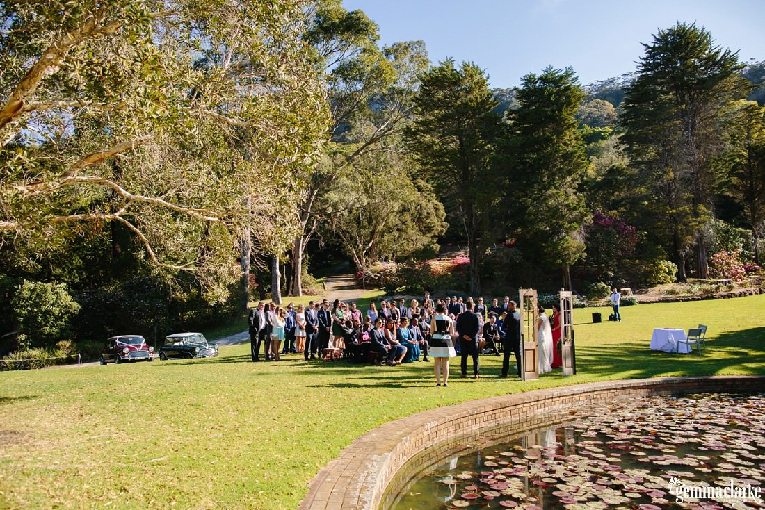 An overall shot of a wedding ceremony in a garden near a pond