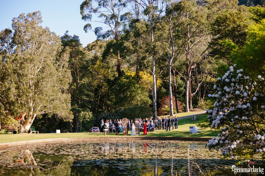 A distant shot of a wedding ceremony in a garden from across a pond
