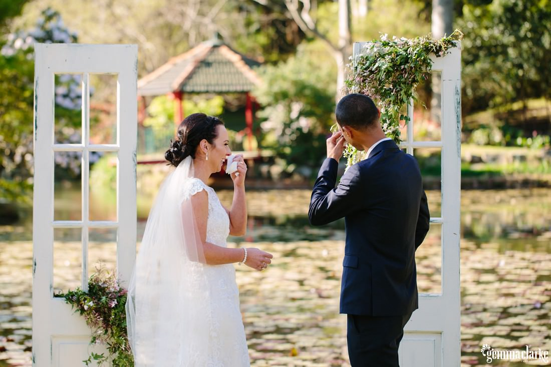A bride and groom both wipe tears from their eyes