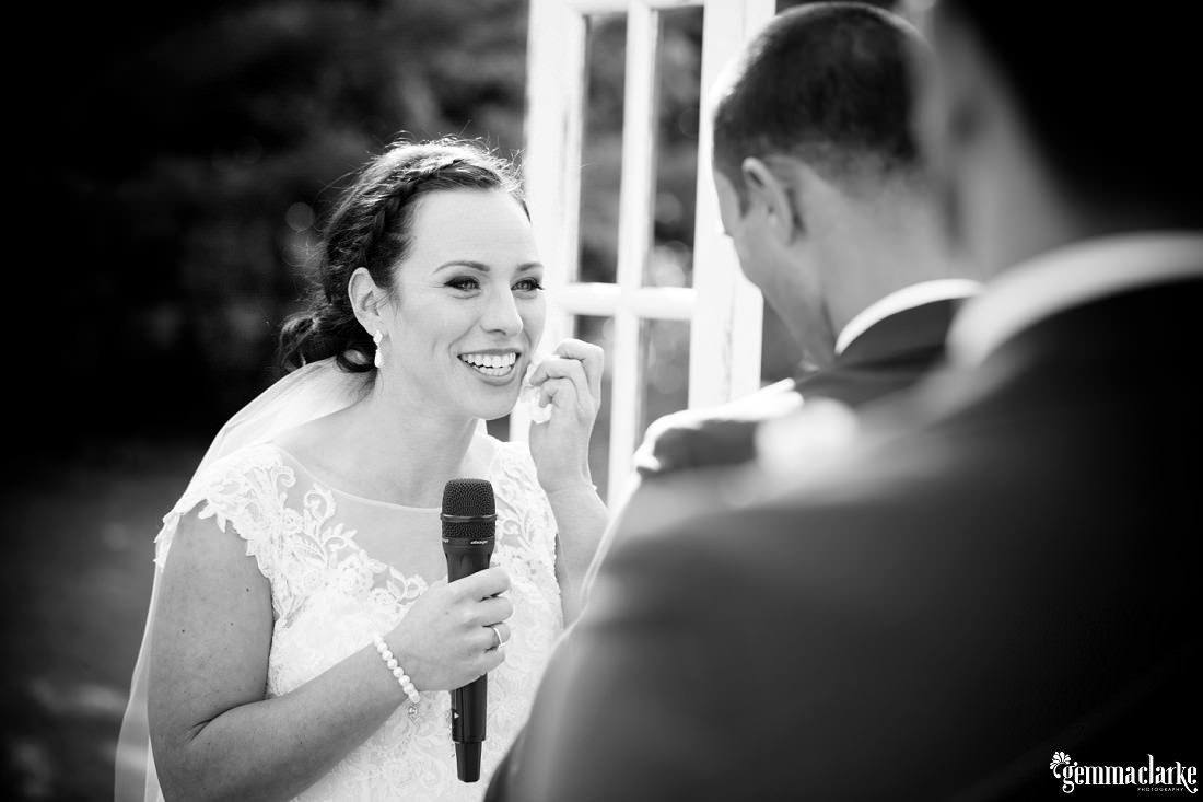 A smiling bride wipes a tear from her face as she speaks into a microphone